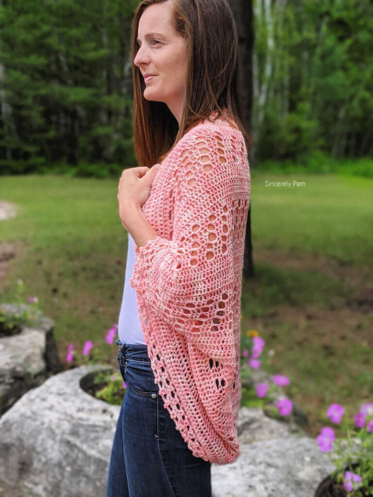 Model is standing in a garden while wearing the Daphne cocoon cardigan crochet pattern by Sincerely Pam