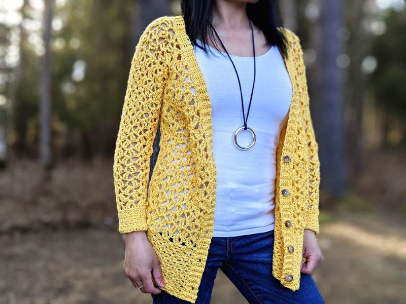 The Addy Lace Cardigan in a bright yellow is worn over a white tank top and jeans. The model is standing in front of a wooded area.