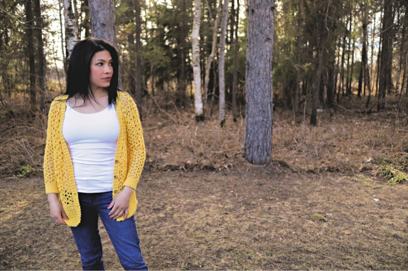 The Addy Lace Cardigan in a bright yellow is worn with the buttons undone, over a white tank top and jeans. The model is standing in front of a wooded area looking off to her left.