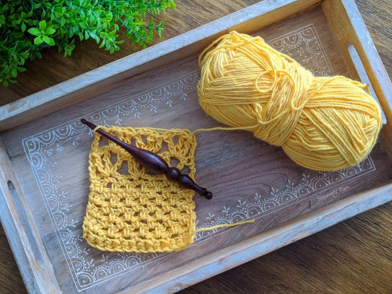 A gauge swatch for the Addy Lace Cardigan using whims merino and an Alpha Series crochet hook.