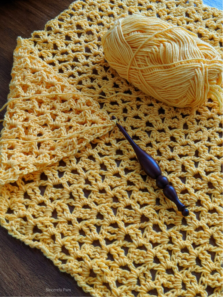 The Back Panel of the Addy Lace Cardigan crochet pattern is being worked up using Whims Merino yarn and an Alpha Series crochet hook.