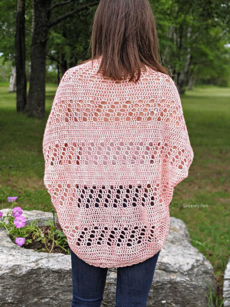 model is standing in a garden with her back to the camera. The daphne cocoon cardigan shows a filet crochet back detail.