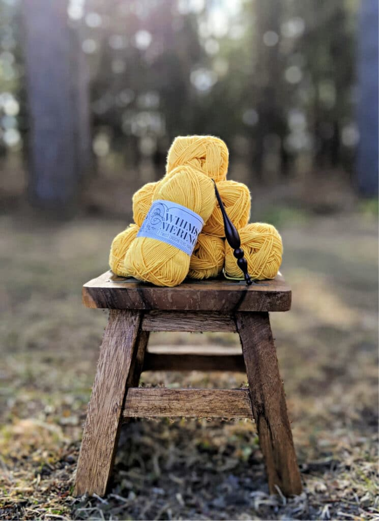 A stack of Whims Merino DK yarn in mustard and an Alpha Hook sit on top of a wooden stool on the grass.