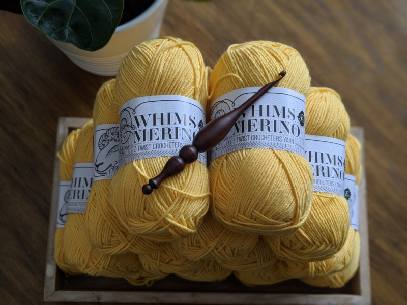 Whims Merino DK in mustard yellow is stacked carefully in a wood tray, with an Alpha Hook placed on top. There is a fiddle leaf fig plant in the top left corner.