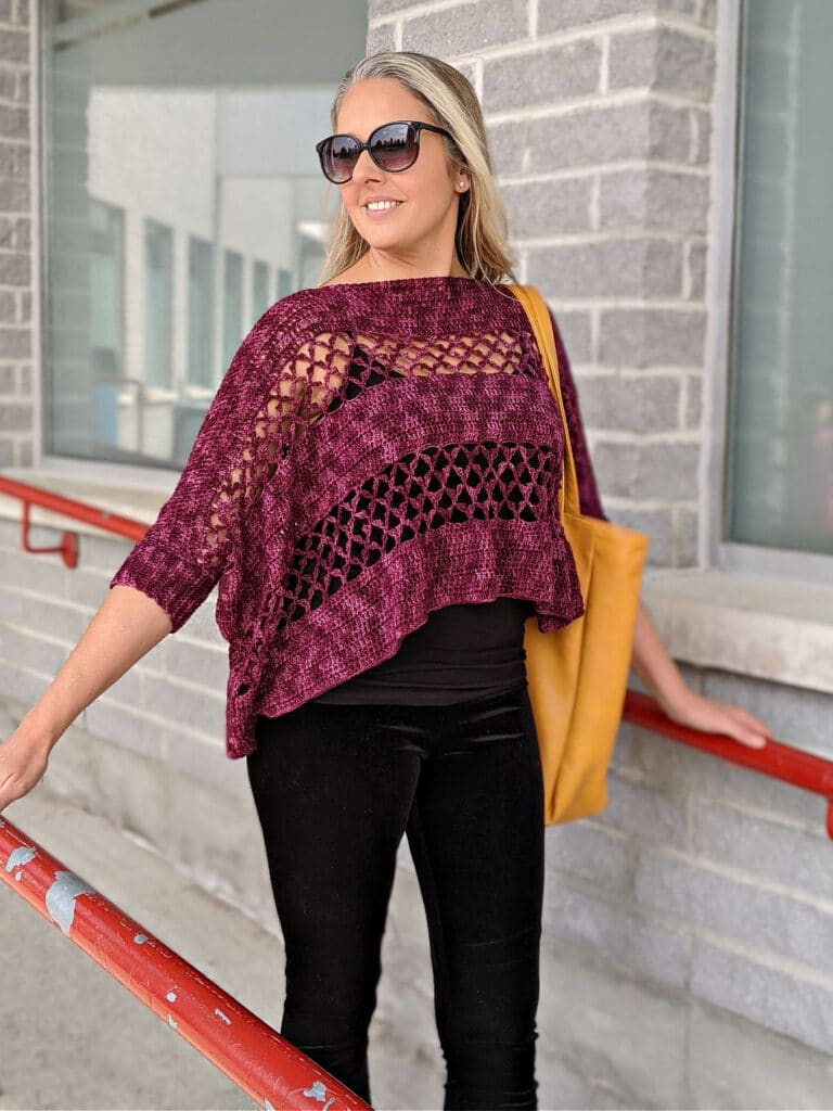 A woman wearing the Contessa Cropped Pullover pattern is walking down a ramp, carrying a WeCrochet tote bag.