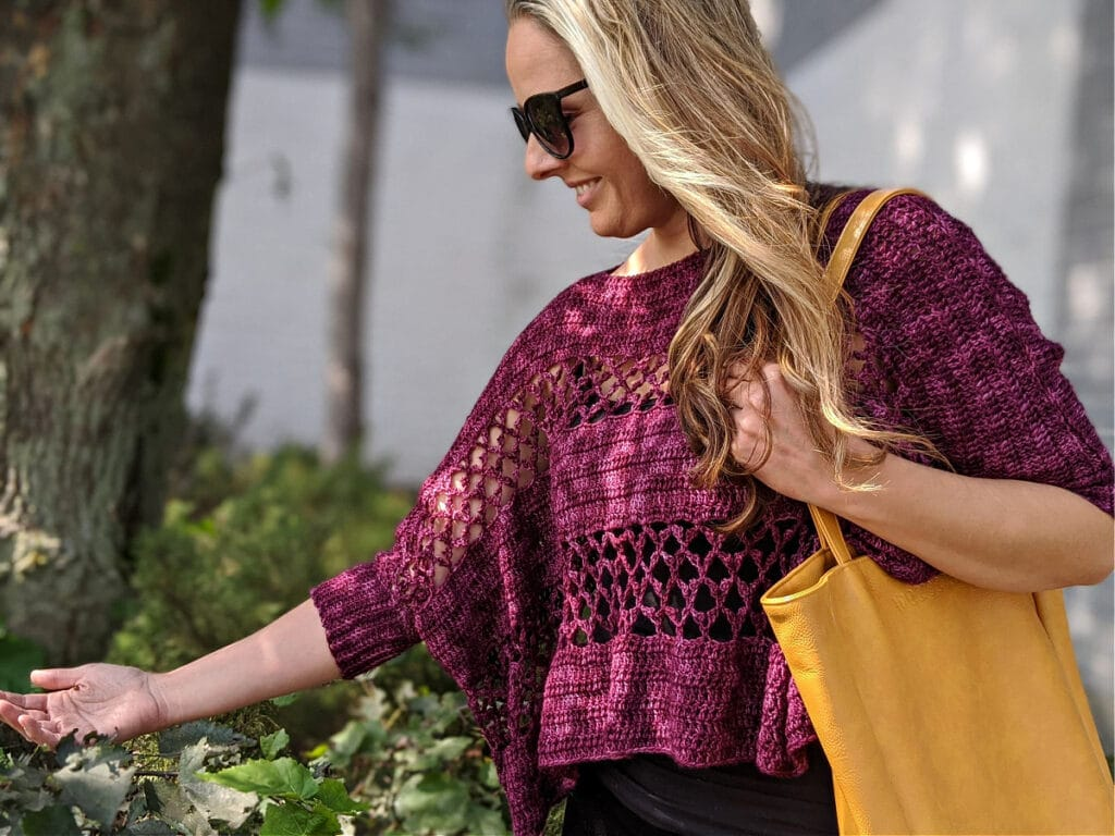 A woman wearing the Contessa Cropped Pullover pattern is touching a leaf, carrying a WeCrochet tote bag.