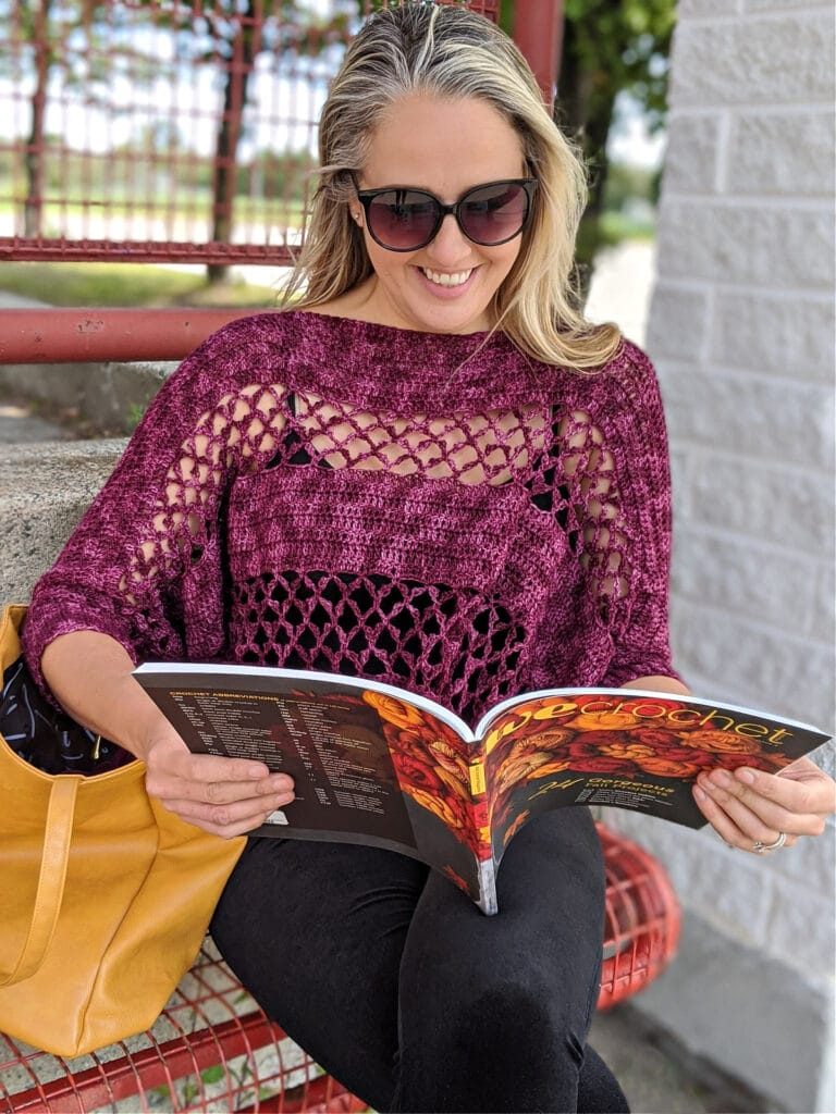 A woman wearing the Contessa Cropped Pullover pattern is sitting on a bench, reading a copy of WeCrochet magazine.