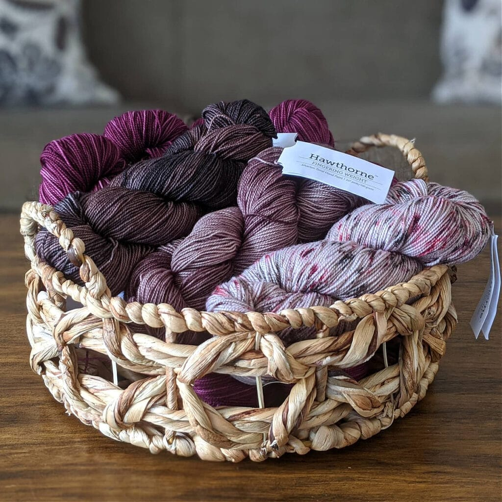 A basket filled with Hawthorne Fingering yarn by WeCrochet sits on a wooden table.