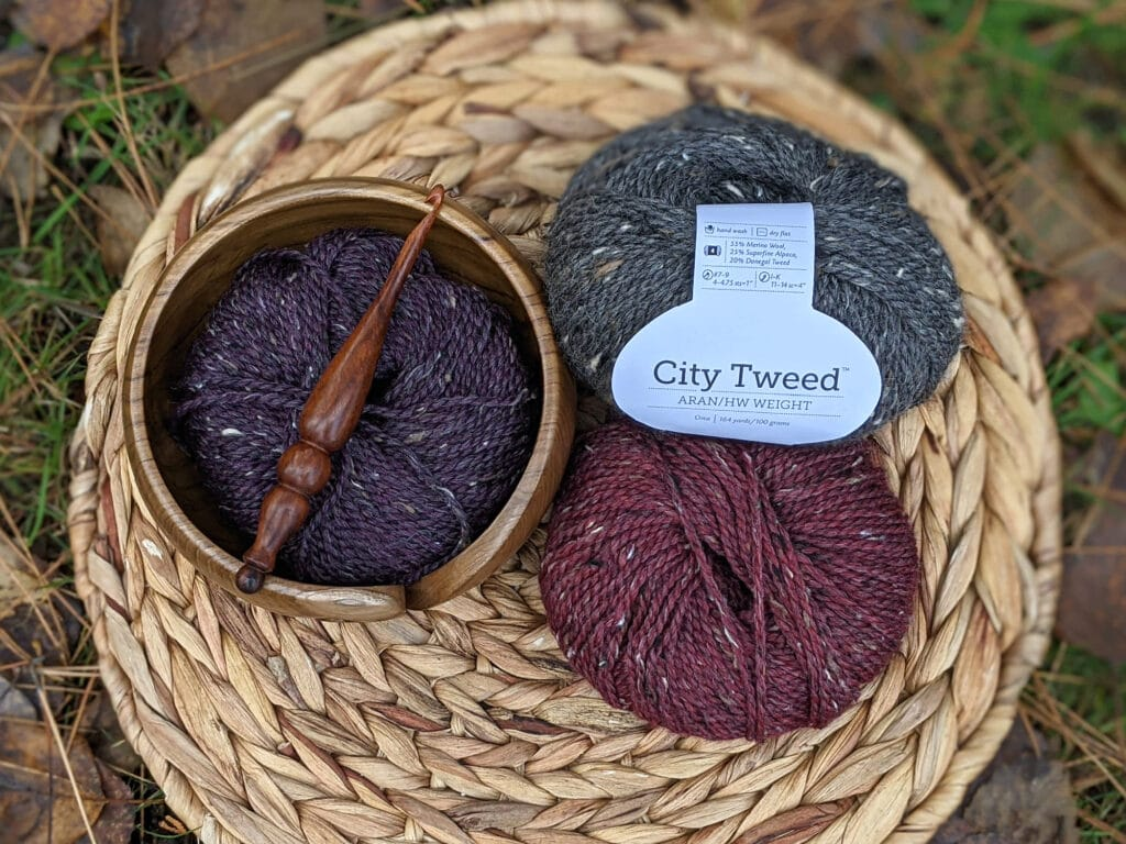 city tweed aran in grey, purple, and maroon are sitting on a wooden circle. A yarn bowl and Alpha series hook from furls crochet lay on top.