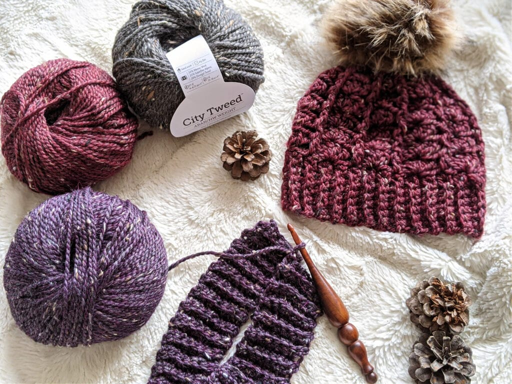 A maroon sarah toque with a fur pompom lays on a white background. An Alpha series crochet is crocheting a second hat in purple. City Tween Aran yarn and pinecones are scattered around.