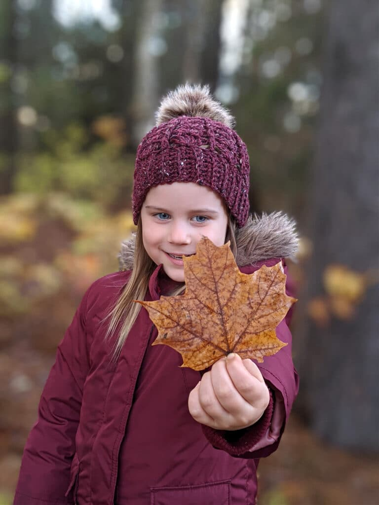 a young girl wears a maroon parka and sarah toque in front of a wooded area.
