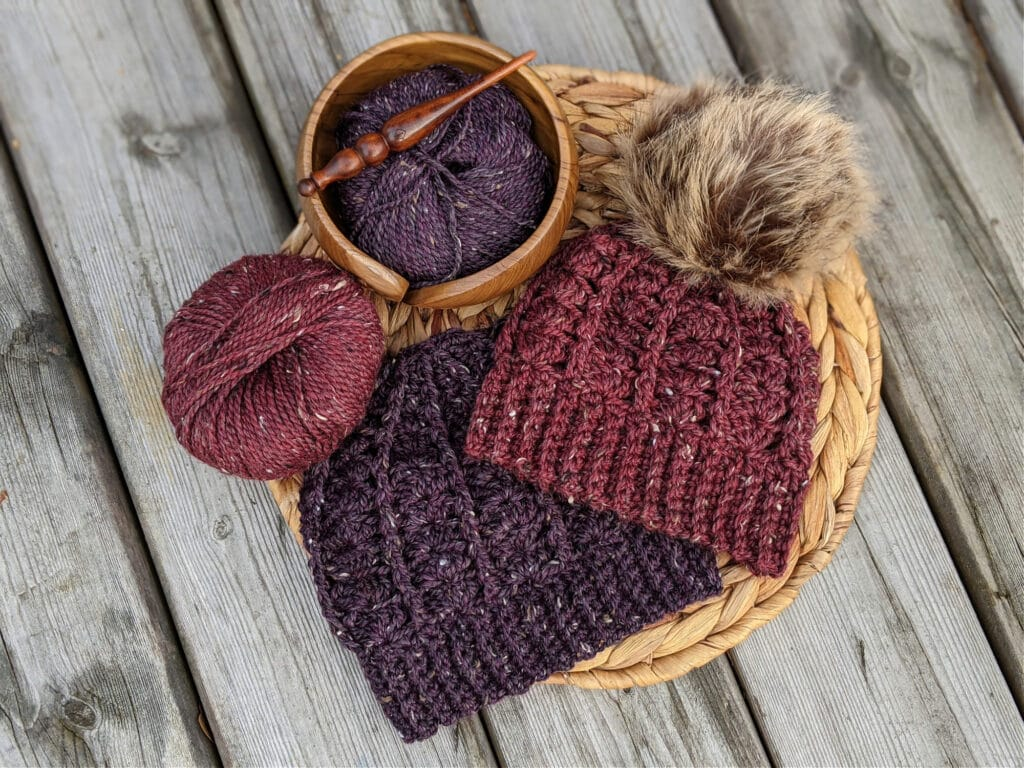 a purple and a maroon sarah toque lay on a wicker mat. City Tweed Aran weight yarn lies in a yarn bowl and on a wood background. An Alpha series crochet hooks lays on top.
