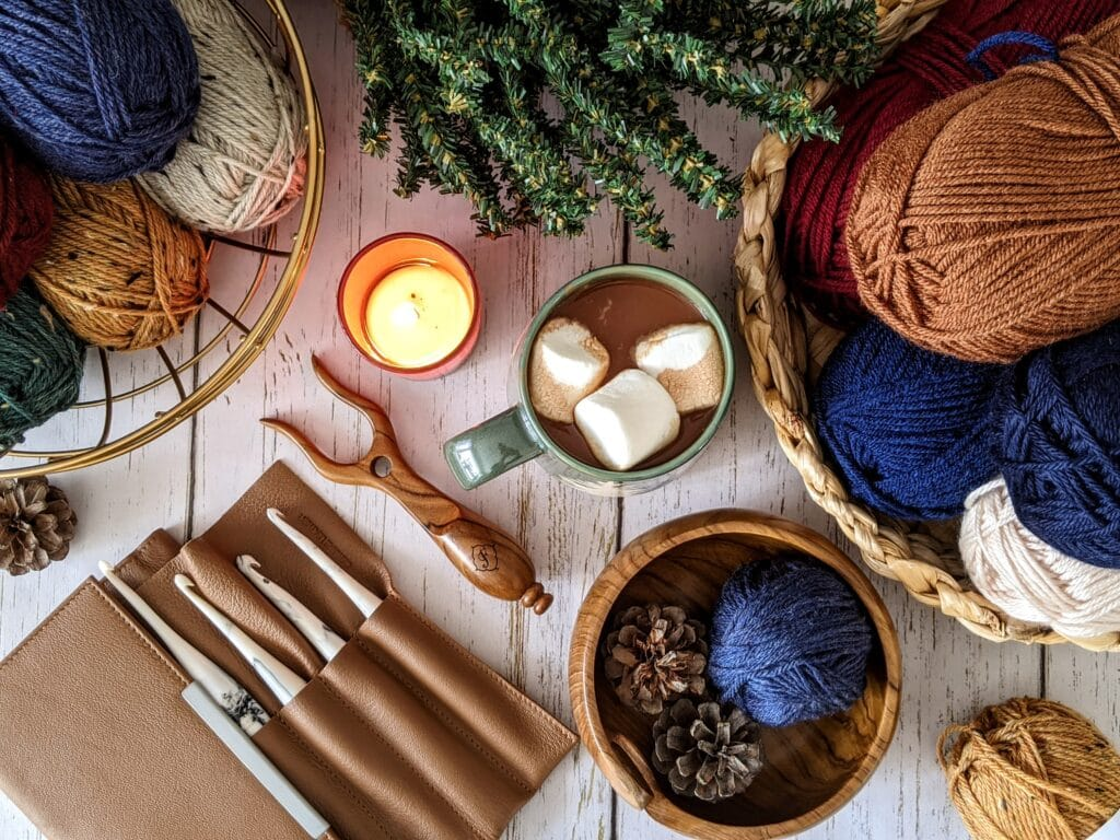 A table top filled with bowls of yarn, crochet hooks, a cup of hot chocolate, and a candle.