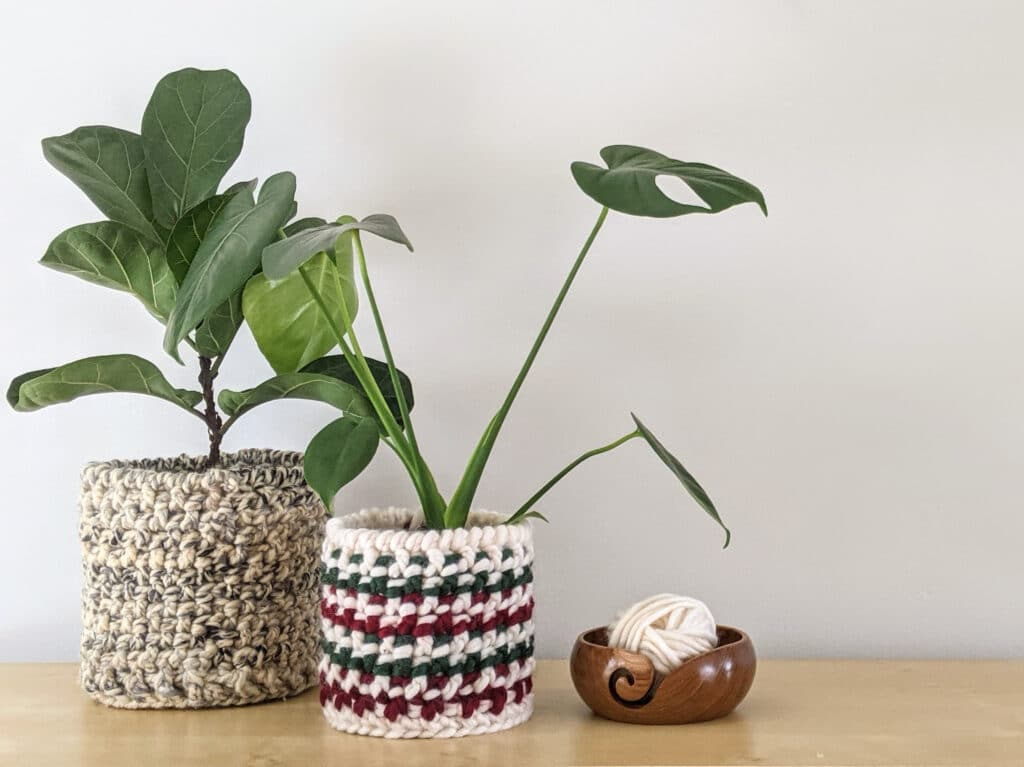 Totally Textured crochet baskets in Lion Brand Wool-ease thick and quick and Tuff Puff yarn sit on a table with plants in them. A teak Furls crochet yarn bowl sits beside them.