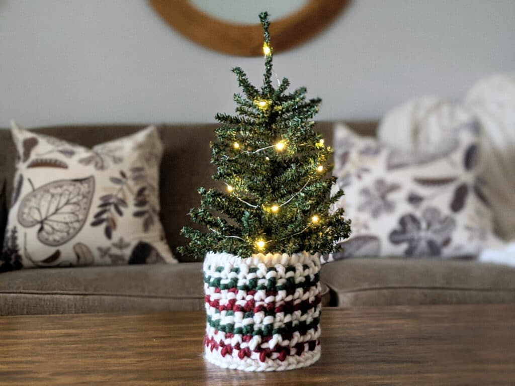 A totally textured crochet basket in Tuff Puff yarn sits on a table holding a mini Christmas tree.