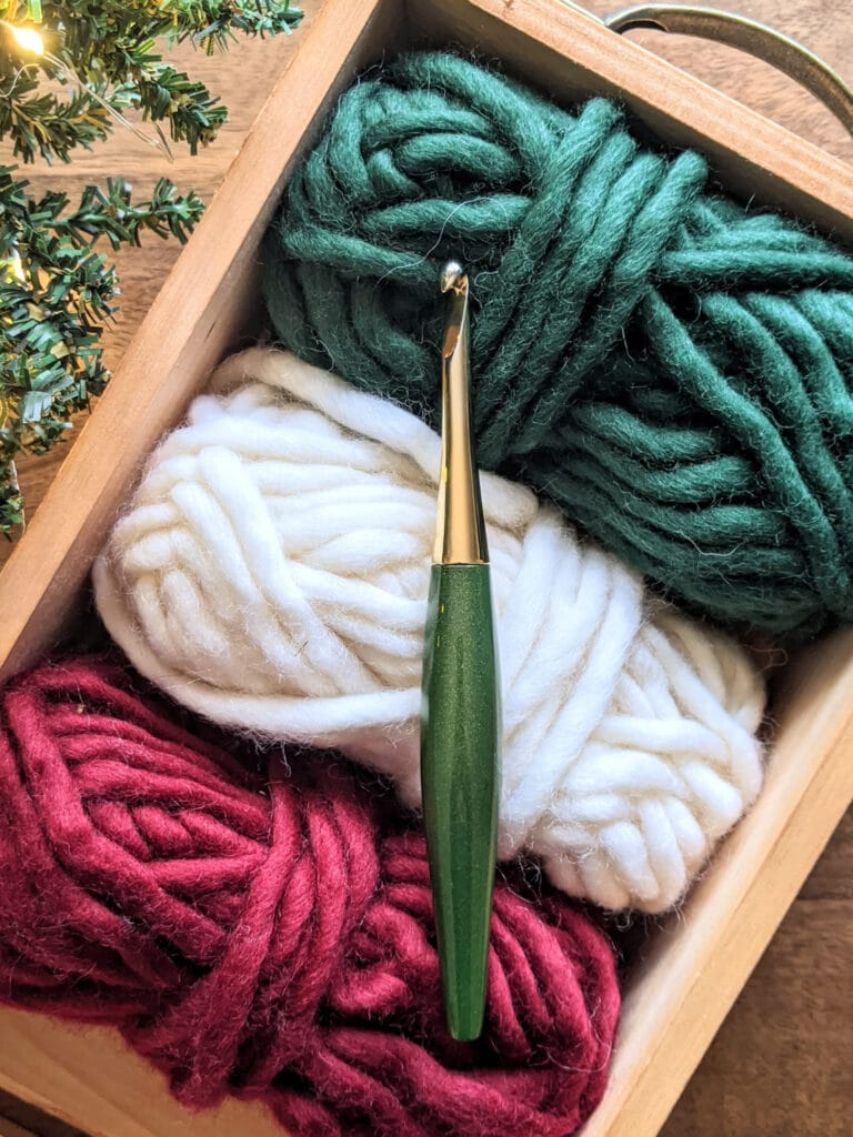 A green Odyssey Furls crochet hook sits on top of a couple balls of WeCrochet Tuff Puff yarn.